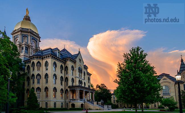 June 11, 2021; Main Building with distant storm clouds (Photo by Matt Cashore/University of Notre Dame)