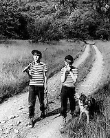 Carefree boys and dog going fishing as they walk down along an unpaved  country road.
