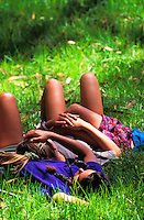 Young girls lying on top of each other resting in a field of grass.