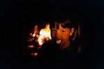 Eight year old girl eats marshmallow in front of campfire.