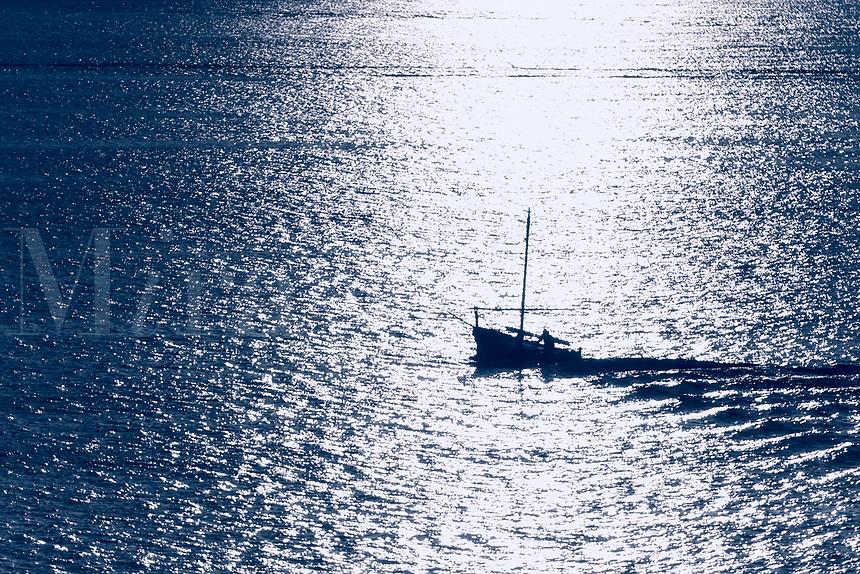 Small fishing boat at sunrise on the Mediterranean Sea, Alghero, Sardinia, Italy.