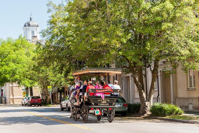 Tourists take a horse-drawn carriage tour on E Bay Street in historic Charleston, South Carolina.