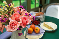 Bouquet of pink rose 'Tiffany' on sun porch with lunch table