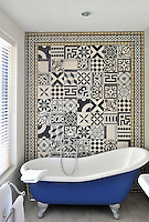 This bathroom in the Paul Cézanne suite of the Hôtel de Gantès in Marseilles is furnished with a slipper bath against a wall of tiles laid in a patchwork pattern