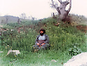 Iraq 1984 .Hama Haji Mahmoud  in a field in Penjwin, watching the sky with  fighters attacking.Irak 1984 .Hama Haji Mahmoud assis dans un champ a Penjwin, regardant les avions de chasse irakiens attaquant