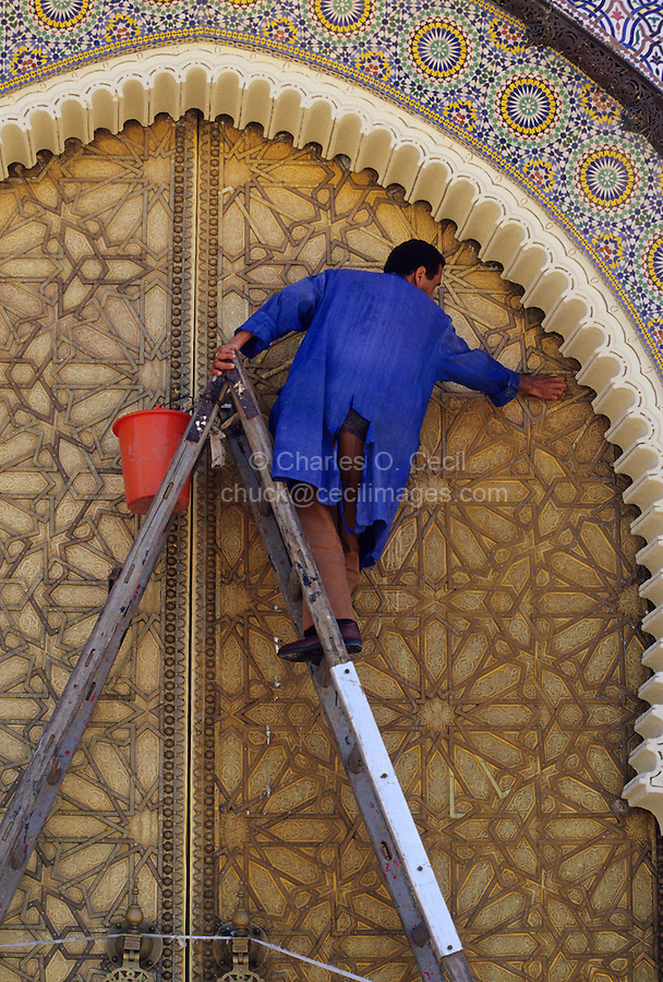 Fez, Morocco - Polishing the doors of the royal palace (Dar El-Makhzen) in Fez.  Orange juice is used.