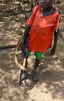 ETHIOPIA, Southern Nations, Lower Omo valley, Kangaten, village Kakuta, Nyangatom tribe, boy with machine gun Kalashnikov AK-47 for protection from cattle raids by hostile neighbor Turkana warriors, the gun is marked with SSPSHQ South Sudan Police Headquarter  / AETHIOPIEN, Omo Tal, Kangaten, Dorf Kakuta, Nyangatom Hirtenvolk, Junge traegt Maschinengewehr Kalaschnikow AK-47 zum Schutz vor Ueberfaellen durch Turkana Krieger, Gewehr hat Markierung SSPSHQ des Sued Sudan