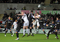 ATTENTION SPORTS PICTURE DESK<br /> Pictured: Albert Serran of Swansea (R in white) heads the ball wide while marked by Joel Ward of Portsmouth (20)<br /> Re: npower Championship, Swansea City FC v Portsmouth Football Club at the Liberty Stadium, south Wales. Friday 26 November 2010
