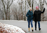 Jane Shipley (left) and Cookie Redfern walk through a light snowfall Thursday, January 7, 2021, on Skyline Drive on Mount Sequoyah in Fayetteville. The two walk regularly in the Fayetteville area including the trail at Gulley Park. Check out nwaonline.com/210108Daily/ and nwadg.com/photos for a photo gallery.<br /> (NWA Democrat-Gazette/David Gottschalk)