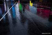 New York, New York<br /> July 10, 2020<br /> <br /> Reflective colorful advertisements in Times Square on a Friday at noon as the tail end of tropical storm Fey rains down on the empty streets with all theaters shuttered for more than 4 months due to the coronavirus pandemic.