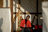 A sick man suffering with ebola-like symptoms waiting in a temporary structure built outside the Connaught Hospital in the hope of being tested and receiving treatment. Since there is no bed capacity at the moment, patients (who potentially pose a great risk) are forced to stay hours and days in a tent outside the hospital without any treatment. The floor of the tent is covered with body liquids which are potentially highly contaminated with ebola virus.