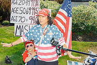 An Asian woman wears Trump 2020 campaign buttons and a hat while talking to a television reporter as alt-right organization Super Happy Fun America demonstrates against facemasks, vaccines, and pandemic closures, and in support of the reelection of President Donald J. Trump near the residence of Massachusetts governor Charlie Baker in Swampscott, Massachusetts, on Sat., Sept. 26, 2020. Super Happy Fun America is most well known for organizing the Straight Pride Parade in Boston on August 31, 2019.