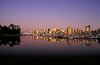 golden reflection of the city skyline in the still waters of Coal Harbour. City Center, downtown, night, Stanley Park, marina, boat, harbour, calm, Canada Place, Trade & Convention Center. Vancouver British Columbia Canada Coal Harbour.