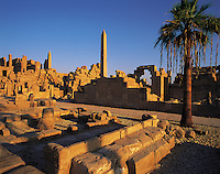 The ruins of Karnak temple, Luxor, Egypt. with obelisks, archway, and palm-tree outlined against a blue sky