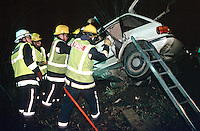 Firefighters attend a road traffic accident where the car was speeding, left the road and plunged down an embankment. It came to rest buried in a tree. The firefighters had to erect a system of ladders to reach and extricate the driver. They are using hydraulic cutting.tools to cut open the vehicle to allow access for the paramedics...© SHOUT. THIS PICTURE MUST ONLY BE USED TO ILLUSTRATE THE EMERGENCY SERVICES IN A POSITIVE MANNER. CONTACT JOHN CALLAN. Exact date unknown.john@shoutpictures.com.www.shoutpictures.com....