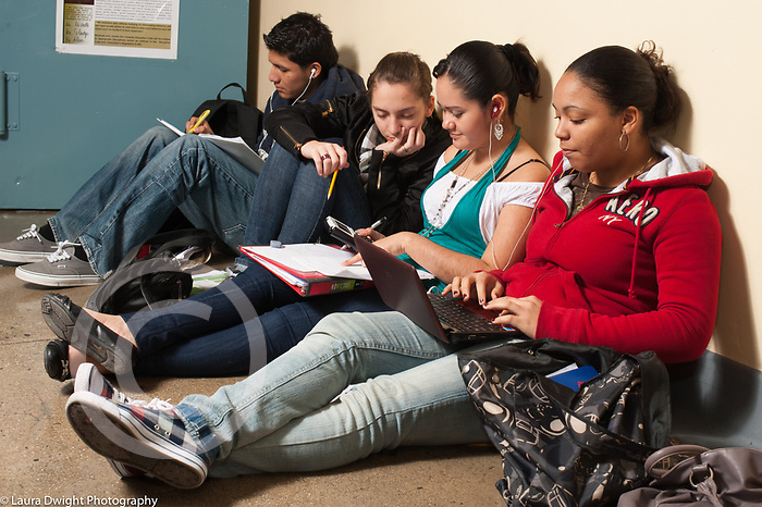 Education High School group of  female and male students studying in school corridor between classes, using laptop computer, notebooks, calculator and writing with pen