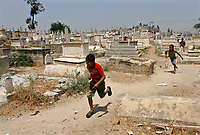 """Gaza.June.22.2008.Mohammed Jilo  a six-year-old  Playing with his brothers  among graves, he was born and grew up in the cemetery , """"he don't go out from this place and he don't fear from the tombs because we live and play here.""""The family was drove out from their original village in the 1948 when Jews forced thousands of Palestinians to migrate, establishing the State of Israe.June.22.2008l.""""photo by Fady Adwan/propaimages"""""""