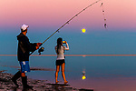 Mika Alexoudis and his wife Emila fish during the full moonrise at Shell Point Beach along the Forgotten Coast of the north Florida panhandle.