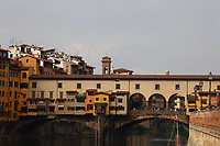 Firenze: A classic view of Ponte Vecchio (the Old Bridge), over the Arno river, with its old peculiar buildings, in the historical center of the town. The photo gives back the colorful atmosphere typical of the place, that is among the town landmarks. There are quite a lot of tourists, too.<br /> <br /> This photo is for Editorial use only.