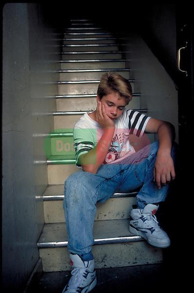 sad teenage boy sitting on stairs