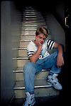 sad teenage boy sitting on stairs