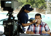 """An assistant wipes Venezuelan President Hugo Chavez's face during his weekly television broadcast """"Alo Presidente"""", in La Guaira, Vargas state near Caracas, August 1, 2004. His recent 200th program could be his last if he loses a referendum on Sunday that asks Venezuelans whether they want him to quit the presidency. REUTERS/Howard Yanes ..TO GO WITH FEATURE  (IMAGE TAKEN AUGUST 01, 2004)"""