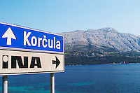 Road sign saying Korcula, view across the sea towards the Peljesac peninsula and the Sveti Ilija mountain. Korcula Island. Korcula Island. Dalmatian Coast, Croatia, Europe.