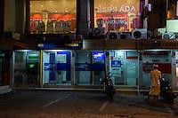 Jimbaran, Bali, Indonesia.  Young Man at Night Preparing to Use an ATM Machine.
