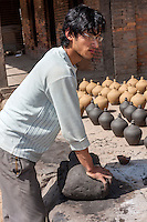Bhaktapur, Nepal.  Young Potter Kneading Clay in Potters' Square.