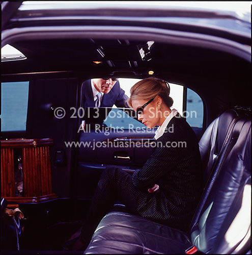 Man looking through limousine window at woman executive<br />