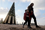 Lebanese people walk beside a Christmas tree with names of those who died during Beirut port explosion, is seen near the damaged grain silo, in Beirut, Lebanon December 22, 2020. Photo by Haitham Moussawi