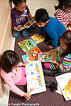 Preschool 3  year olds group of children looking at books separately vertical