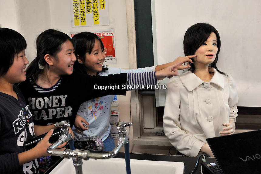 Pupils touch the world's first robot teacher, Saya, in a Tokyo pimary school, 7th May 2009, after a lesson. SAYA has been in development the for the past 15 years by Professor Hiroshi Kobayashi at the Dept. of Mechanical Engineering at Tokyo University of Science.  SAYA can talk and has a full range of facial expressions. Professor Hiroshi Kobayashi's study, at the Dept. of Mechanical Engineering at Tokyo University of Science.