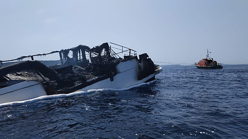 What's left of the 29m Sanlorenzo yacht Reine d'Azur is towed away after the fire was brought under control