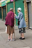 Two elderly women with walking sticks chat in Church Street, London.