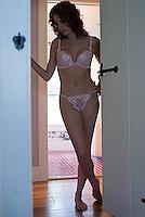 Woman wearing lingerie standing in hallway<br />