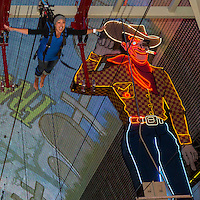 Las Vegas, Nevada.  Fremont Street.  Female Zip Line Rider on the Zoomline Approaching Cowboy Sign.
