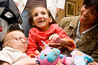Marie Francisco and her daughter Amanda with Amy Orr, left,  at the Share and Care Network's annual retreat held at the Doubletree Guest Suites Hotel in Boston on May 20, 2006. <br /> <br /> The Share and Care Network was created in 1981 by Pat Cahill when her son Scott was diagnosed with Cockayne Syndrome.  A rare form of dwarfism, Cockayne Syndrome is a genetically determined condition whose symptoms include microcephaly, mental retardation, progressive blindness, progressive hearing loss, premature aging, and a shortened lifespan averaging 18 years.  Those afflicted have distinctive facial features, including sunken eyes, pinched faces, and protruding jaws as well as distinctive gregarious, affectionate personalities.<br /> <br /> Because of the rarity of the condition (1/1,000 live births) and its late onset (characteristics usually begin to appear only after one year), many families and physicians are often baffled by children whose health begins to deteriorate after normal development.  It was partly with this in mind that the Share and Care Network was formed, to promote awareness of this disease as well as to provide a support network for those families affected.  In 1998 it began organizing an annual retreat, which has grown from three families in its inaugural year to more than 30 today.  Although the retreat takes place in the United States, families from as far as Japan arrive for this one weekend out of the year to share information and to support one another.