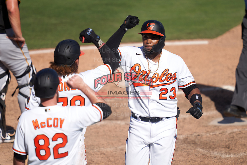 Baltimore Orioles Yusniel Diaz (23) celebrates with Jahmai Jones (78) and Mason McCoy (82) after hitting a home run during a Major League Spring Training game against the Pittsburgh Pirates on February 28, 2021 at Ed Smith Stadium in Sarasota, Florida.  (Mike Janes/Four Seam Images)