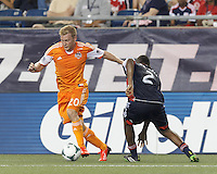 Houston Dynamo midfielder Andrew Driver (20) on the attack.  In a Major League Soccer (MLS) match, Houston Dynamo (orange) defeated the New England Revolution (blue), 2-1, at Gillette Stadium on July 13, 2013.