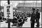 """Accused peasants are kept under guard by local militia as they wait to be denounced at a mass rally as one of the """"four elements"""" - landlords, rich peasants, counterrevolutionaries, or """"bad characters"""" - as indicated by the sign. Liaodian commune, Acheng county, 13 May 1965"""