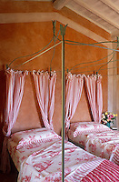 A pair of wrought-iron four-poster beds is dressed in pink toile de Jouy linen with pink and white striped curtains
