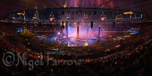 "27 JUL 2012 - LONDON, GBR - Four orange rings begin to move from the top of the stadium as workers begin to forge a fifth during the ""Pandemonium"" section of the Opening Ceremony of the London 2012 Olympic Games in the Olympic Stadium in the Olympic Park, Stratford, London, Great Britain (PHOTO (C) 2012 NIGEL FARROW)"