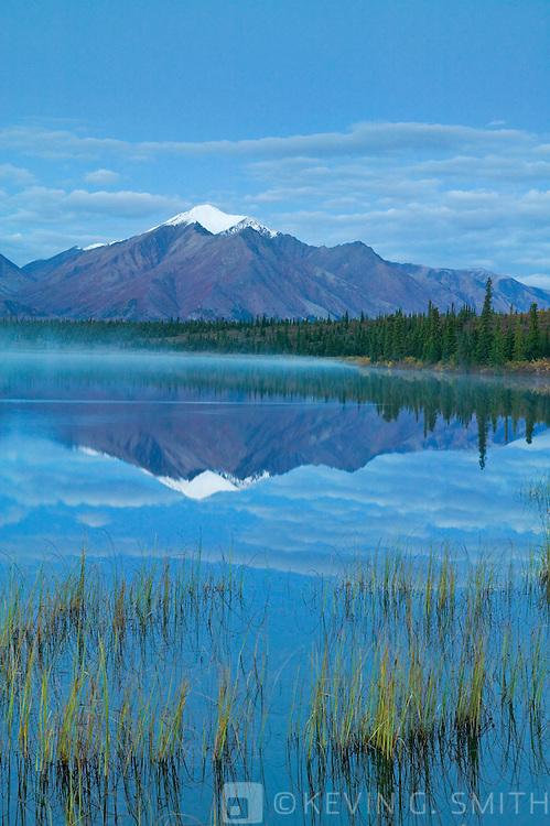 Mountain reflected  in Drasher Lake before dawn, Denali Highway, fall Alaska, USA