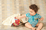 10 month old baby boy finding toy ball hidden under cloth