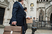 Legal workers arrive at the Royal Courts of Justice, London.