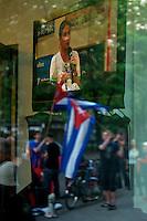 """Protest gegen einen Auftritt der Cubanischen Bloggerin Yoani Sanchez im Instituto Cervantes in Berlin.<br />Die Cubanische Bloggerin Yoani Sanchez redete auf Einladung der Jounalistenorganisation Reporter ohne Grenzen und der Tageszeitung """"taz"""" am Mittwoch den 8. Mai 2013 im Instituto Cervantes. Gegen diesen Auftritt protestierten vor dem Gebaeude Mitglieder verschiedener kommunistischer Organisationen aus Lateinamerika und Deutschland.<br />Im Bild: Im Gebaeude des Instituto Cervantes wird auf einem Grossbildfernseher die Veranstaltung uebetragen, waehrend vor der Tuer die Gegendemonstranten stehen.<br />8.5.2013, Berlin<br />Copyright: Christian-Ditsch.de<br />[Inhaltsveraendernde Manipulation des Fotos nur nach ausdruecklicher Genehmigung des Fotografen. Vereinbarungen ueber Abtretung von Persoenlichkeitsrechten/Model Release der abgebildeten Person/Personen liegen nicht vor. NO MODEL RELEASE! Don't publish without copyright Christian-Ditsch.de, Veroeffentlichung nur mit Fotografennennung, sowie gegen Honorar, MwSt. und Beleg. Konto:, I N G - D i B a, IBAN DE58500105175400192269, BIC INGDDEFFXXX, Kontakt: post@christian-ditsch.de<br />Urhebervermerk wird gemaess Paragraph 13 UHG verlangt.]"""