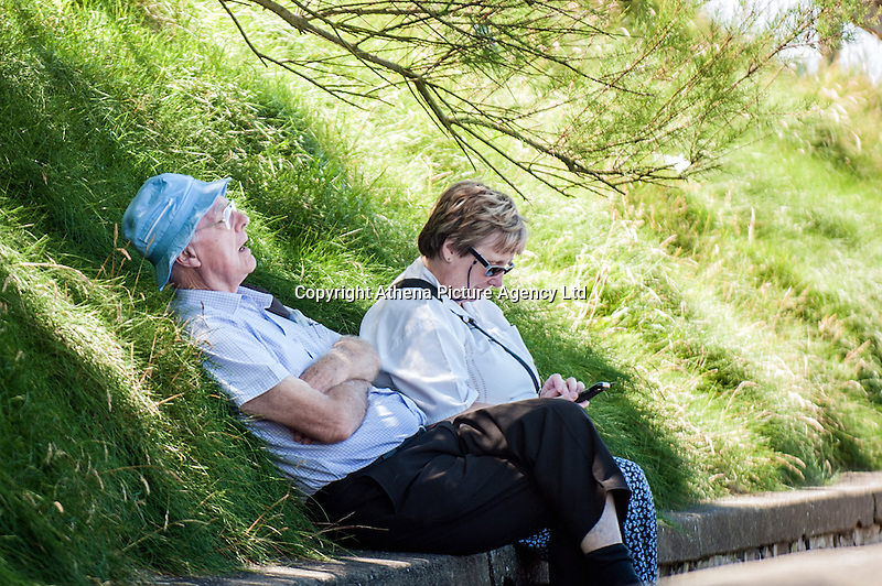 UK Weather: Aberystwyth, Ceredigion, West Wales Monday 18th July 2016. A couple rest in the hade by the promenade. The RNLI are out in force both making sure people are safe and raising awareness of the work they do.  Although it is overcast the sun is breaking through and the temperatures are expected to hit the low 20C with the mini heat wave expected to continue tomorrow reaching 30