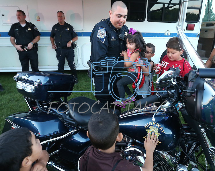 Nevada Highway Patrol Trooper Mike Ortega helps Lilah Torres, 3, check out his motorcycle during the 14th annual National Night Out in Carson City, Nev., on Tuesday, Aug. 2, 2016. <br />Photo by Cathleen Allison