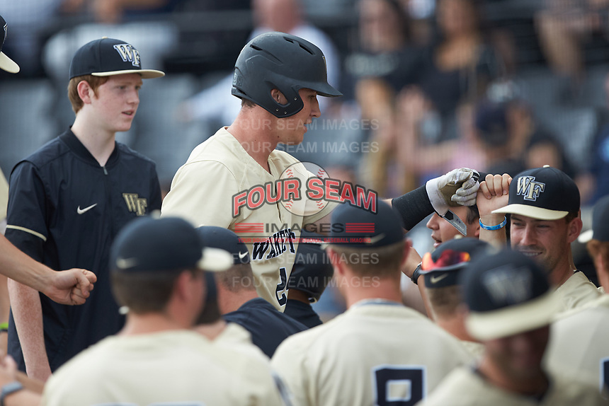 Chris Lanzilli (24) of the Wake Forest Demon Deacons is greeted by his teammates as he returns to the dugout after scoring a run during the game against the Virginia Cavaliers at David F. Couch Ballpark on May 19, 2018 in  Winston-Salem, North Carolina. The Demon Deacons defeated the Cavaliers 18-12. (Brian Westerholt/Four Seam Images)